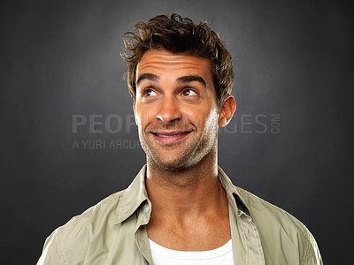 Buy stock photo Closeup of young man looking up and smiling on black background