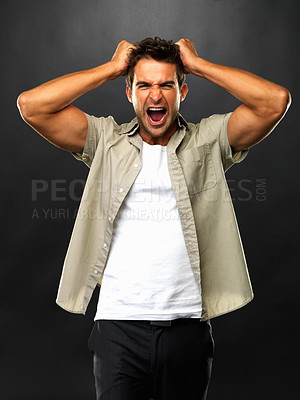 Buy stock photo Portrait of man pulling his hair and screaming on black background