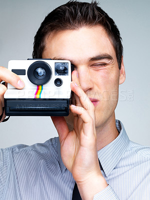 Buy stock photo Portrait of a young male photographer using a camera against grey background