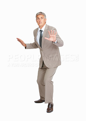 Buy stock photo Studio shot of a mature businessman trying to save himself from something against a white background