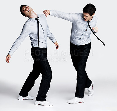 Buy stock photo Full length image of a psycho young male entrepreneur fighting with himself against grey background