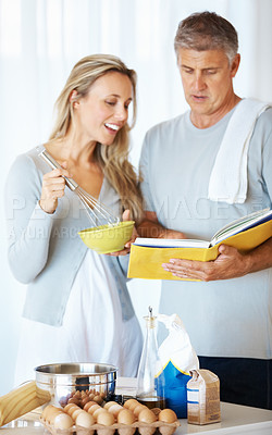 Buy stock photo Portrait of man and woman preparing batter with help of recipe book in kitchen at home