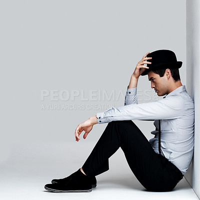Buy stock photo Profile image of a young man lost in deep thought while sitting on the floor against grey background