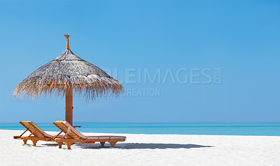 Buy stock photo An attractive image of two chairs and umbrella on the beach - copyspace