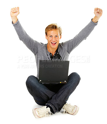 Buy stock photo Studio shot of a young man using a laptop with his arms raised in celebration