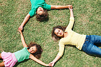 Top view of kids holding hands and lying on grass