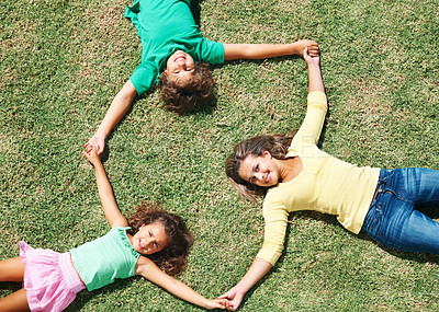 Buy stock photo Top view of happy children holding hands and lying on grass , forming a circle