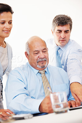 Buy stock photo Portrait of confident business team sitting at the table and looking at a document in the office