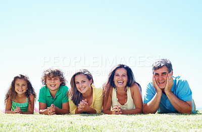 Buy stock photo Mother, father, son and two daughters smiling, lying on grass - copyspace