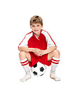 Cute little boy in uniform sitting on a football