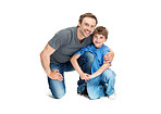 Happy young father and son sitting together on white