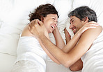 Playful middle aged couple relaxing on bed