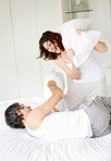 Happy mature couple fighting with pillows in bed