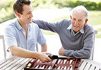 Happy father and son playing backgammon in a park