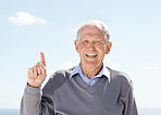 Smiling senior man pointing upwards - Outdoor