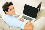 Relaxed young guy using laptop at home