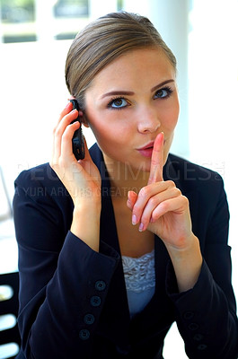 Buy stock photo Portrait of a young businesswoman on the phonenwith her finger on her lips