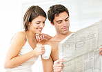 Beautiful young couple reading newspaper together