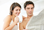 Attractive young couple reading newspaper