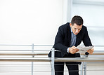 Business man reading a newspaper by a railing