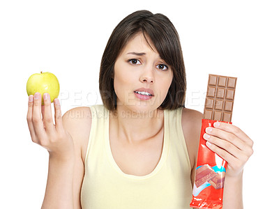 Buy stock photo Choice - Confused young female holding an apple and a bra of chocolate against white