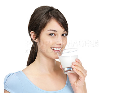 Buy stock photo Portrait of a cute young female drinking a glass of milk isolated against white
