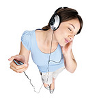 Top view of a young female listening to music over headphones