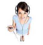 Top view of a smiling female enjoying music on headphones