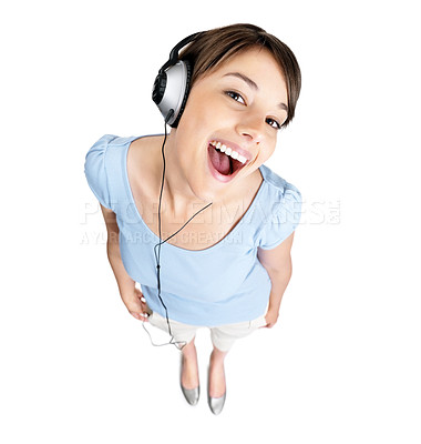 Buy stock photo Top view of an excited young female listening to music on headphones