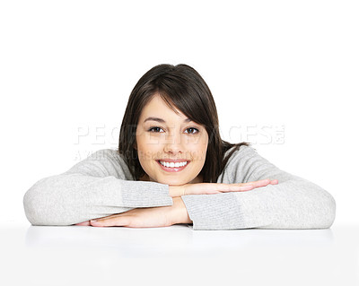 Buy stock photo Portrait of a charming young female leaning on a table on white background