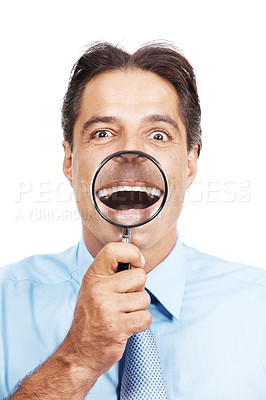 Buy stock photo Studio portrait of a businessman holding a magnifying glass in front of his mouth