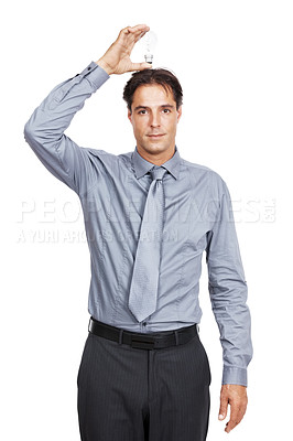 Buy stock photo Shot of a businessman holding a lightbulb over his head against a white background