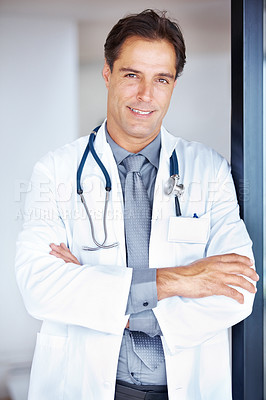 Buy stock photo Portrait of a confident mature male doctor standing with hand folded