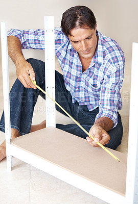 Buy stock photo Busy carpenter measuring a wooden plank with tape measure in workshop