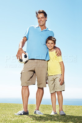 Buy stock photo Full length of happy man holding a football with his cute son on grass field on a sunny day