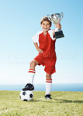 Buy stock photo Portrait of an excited little football champion showing his winners trophy standing on the field