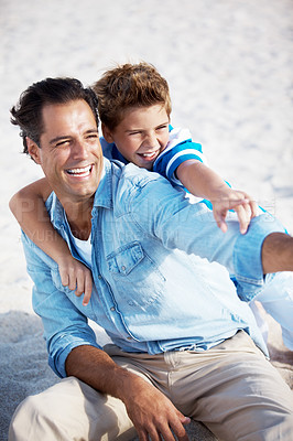 Buy stock photo Smiling father and son pointing at something interesting a the sea shore on a summer day