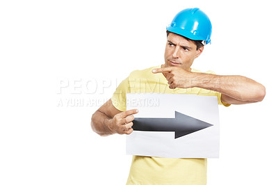 Buy stock photo Shot of a construction worker pointing to the left while holding a sign with an arrow pointing to the right on it