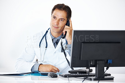Buy stock photo Thoughtful mature doctor making a phone call with patient while sitting at his office desk - Copyspace