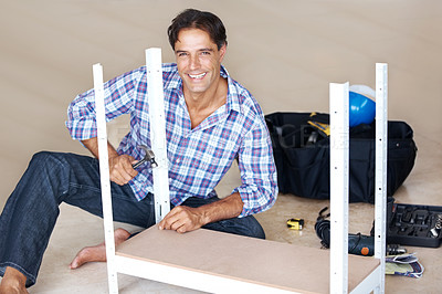 Buy stock photo A handsome man smiling at the camera while assembling a shelf