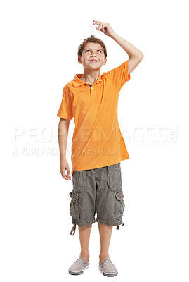 Buy stock photo Full length portrait of happy young boy holding a electric bulb over his head against white background