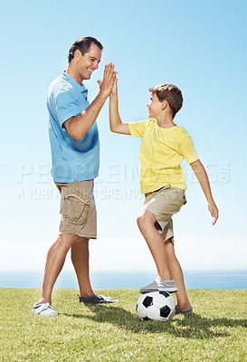 Buy stock photo Happy man giving high five to his little son with a soccer ball - Outdoors