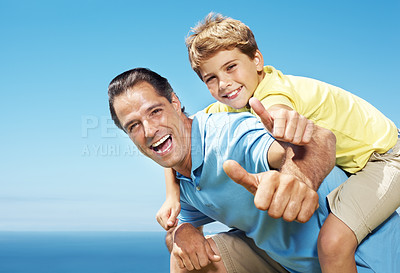 Buy stock photo Portrait of a happy mature man giving his son piggy back ride and geturing thumbs up sign - Outdoor