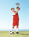 Little football champ holding up his winning trophy