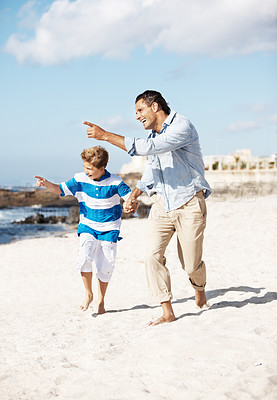 Buy stock photo Father and son walking on the beach and pointing away at something interesting