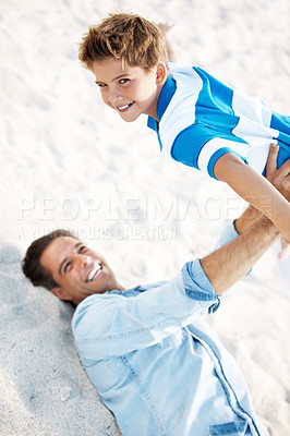 Buy stock photo Happy father lying down and holding his son in the air at the beach
