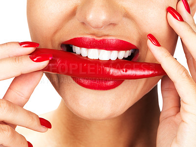 Buy stock photo Cropped image of a young lady holding red chilli in mouth