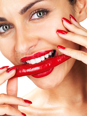 Buy stock photo Closeup portrait of a cute young woman holding red hot chilli in mouth