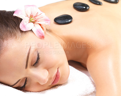 Buy stock photo Hot stone massage in the day spa - Portrait of a beautiful young woman at the day spa with black stones on her bare back