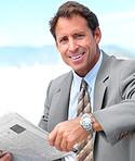 Business man holding newspaper sitting outside